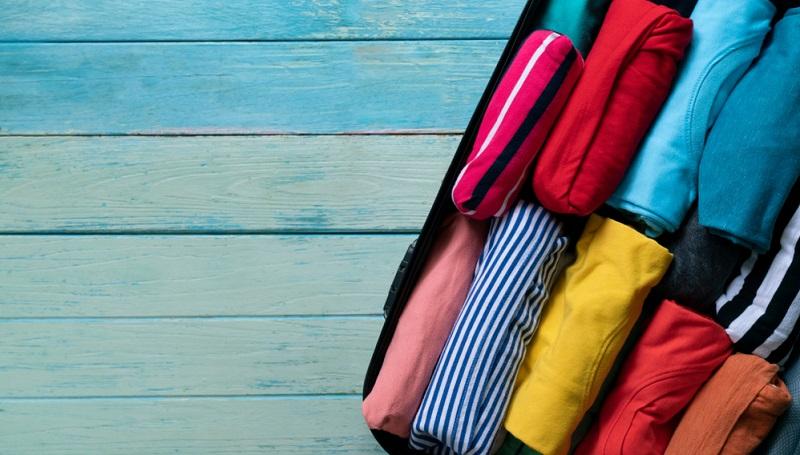 Koffer packen: Wenn man Kleidungsstücke zusammenrollt, passt wesentlich mehr ins Gepäck.